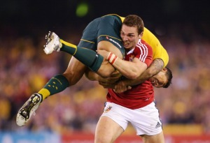 MELBOURNE, AUSTRALIA - JUNE 29: George North of the Lions lifts Israel Folau of Wallabies while carrying the ball during game two of the International Test Series between the Australian Wallabies and the British & Irish Lions at Etihad Stadium on June 29, 2013 in Melbourne, Australia. (Photo by Matt King/Getty Images for HSBC)